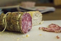 Creative Commons Licensed photograph of a Salami sausage with a slice cut off it.